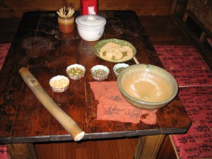 To make lui cha, pound tea leaves, nuts, and seeds in a bowl with a stick.